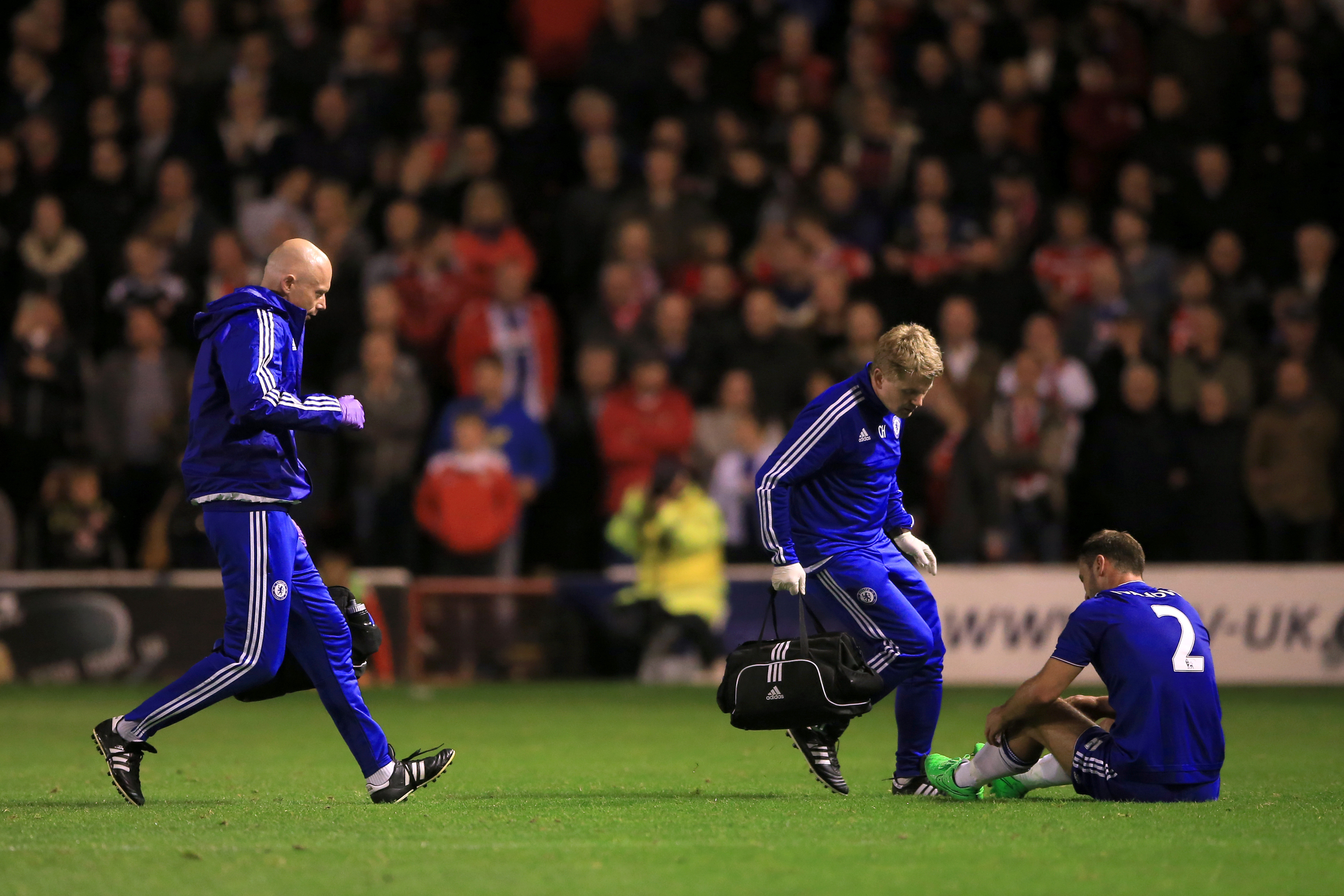 Chelsea doctor Chris Hughes (centre) and physiotherapist Steven Hughes (left) enter the field of play to treat Branislav Ivanovic during the Capital One Cup, third round match at Banks' Stadium, Walsall.